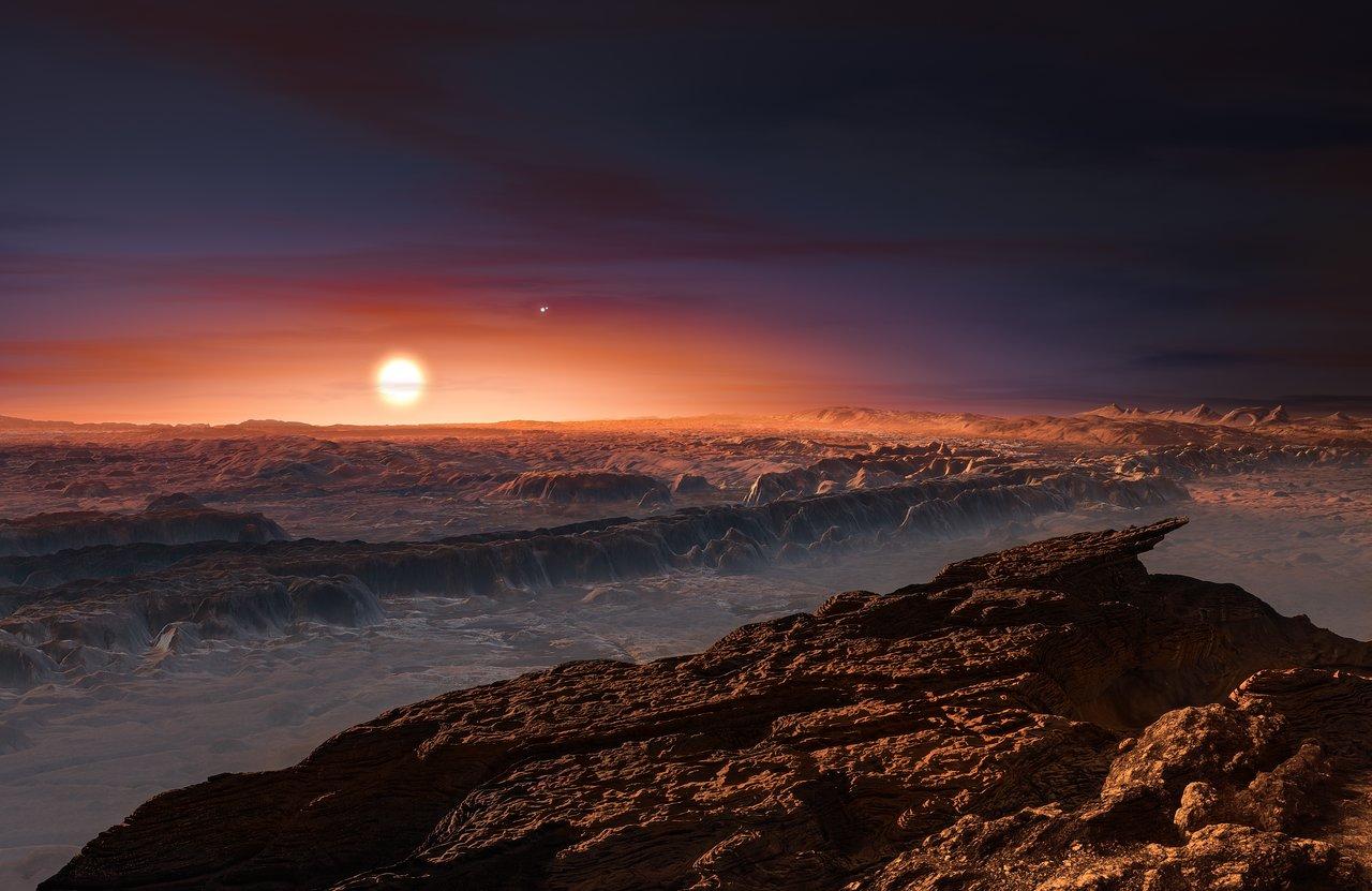 Wizja artystyczna prezentuje widok powierzchni planety Proxima b, okrążającej czerwonego karła Proxima Centauri, najbliższą gwiazdę względem Układu Słonecznego. Gwiazda podwójna Alfa Centauri AB także jest widoczna naobrazku, naprawo, wgórę odProximy. Proxima b jest nieco bardziej masywna niż Ziemia ikrąży wekosferze (tzw. strefie życia) wokół Proximy Centauri, gdzie panuje temperatura odpowiednia dla występowania wody wstaniej ciekłym napowierzchni planety.