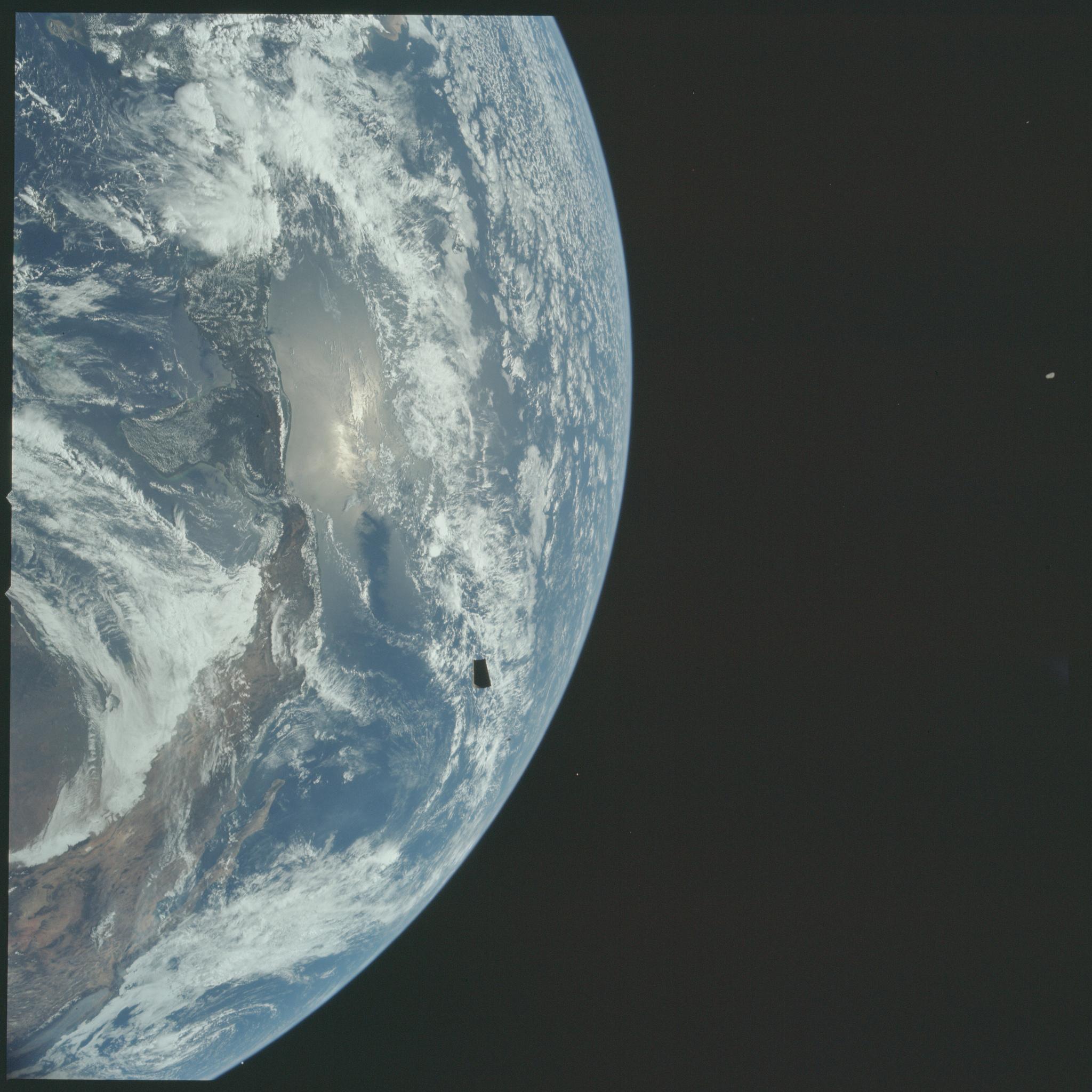 Fotografia Ziemi wykonana podczas misji Apollo 12. Na tle planety możemy zaobserwować jeden z czterech paneli adaptera odrzucanych podczas transpozycji i dokowania.