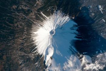 Śnieg ichmury wyróżniają zielone pola wokół góry Fuji wJaponii. Zdjęcie z8 lutego 2016 roku.
