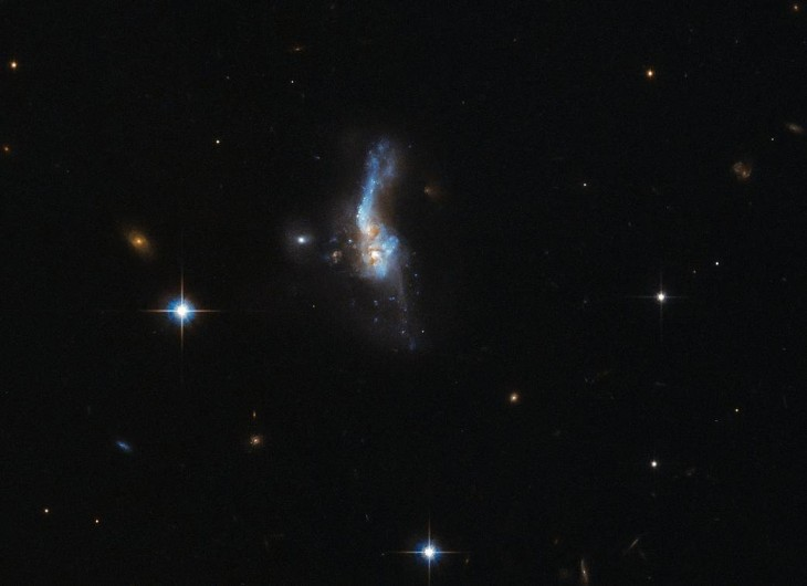 This delicate smudge in deep space is far more turbulent than it first appears. Known as IRAS 14348-1447 — a name  derived in part from that of its discoverer, the Infrared Astronomical Satellite (IRAS for short) — this celestial object is actually a combination of two gas-rich spiral galaxies. This doomed duo approached one another too closely in the past, gravity causing them to affect and tug at each other and slowly, destructively, merge into one. The image was taken by Hubble's Advanced Camera for Surveys (ACS). IRAS 14348-1447 is located over a billion light-years away from us. It is one of the most gas-rich examples known of an ultraluminous infrared galaxy, a class of cosmic objects that shine characteristically — and incredibly — brightly in the infrared part of the spectrum. Almost 95% of the energy emitted by IRAS 14348-1447 is in the far-infrared!  The huge amount of molecular gas within IRAS 14348-1447 fuels its emission, and undergoes a number of dynamical processes as it interacts and moves around; these very same mechanisms are responsible for IRAS 14348-1447's own whirling and ethereal appearance, creating prominent tails and wisps extending away from the main body of the galaxy.