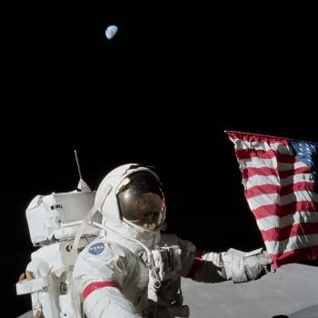 Gene Cernan pozuje do zdjęcia z flagą Stanów Zjednoczonych.