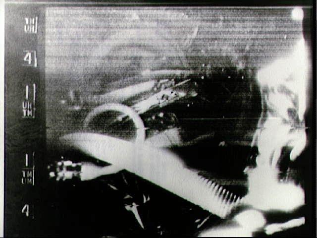 """W tle można dostrzec twarz Gordo Coopera, choć bardziej widoczny jest jego hełm. Ujęcie zostało wykonane przez kamerę, która znajdowała się wewnątrz kapsuły """"Faith 7""""."""