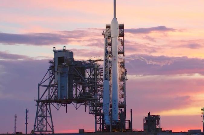 Flagowy statek SpaceX na tle podświetlanych przez zachodzące Słońce chmur, przez które początek poniedziałkowego odliczania został przełożony o prawie godzinę,