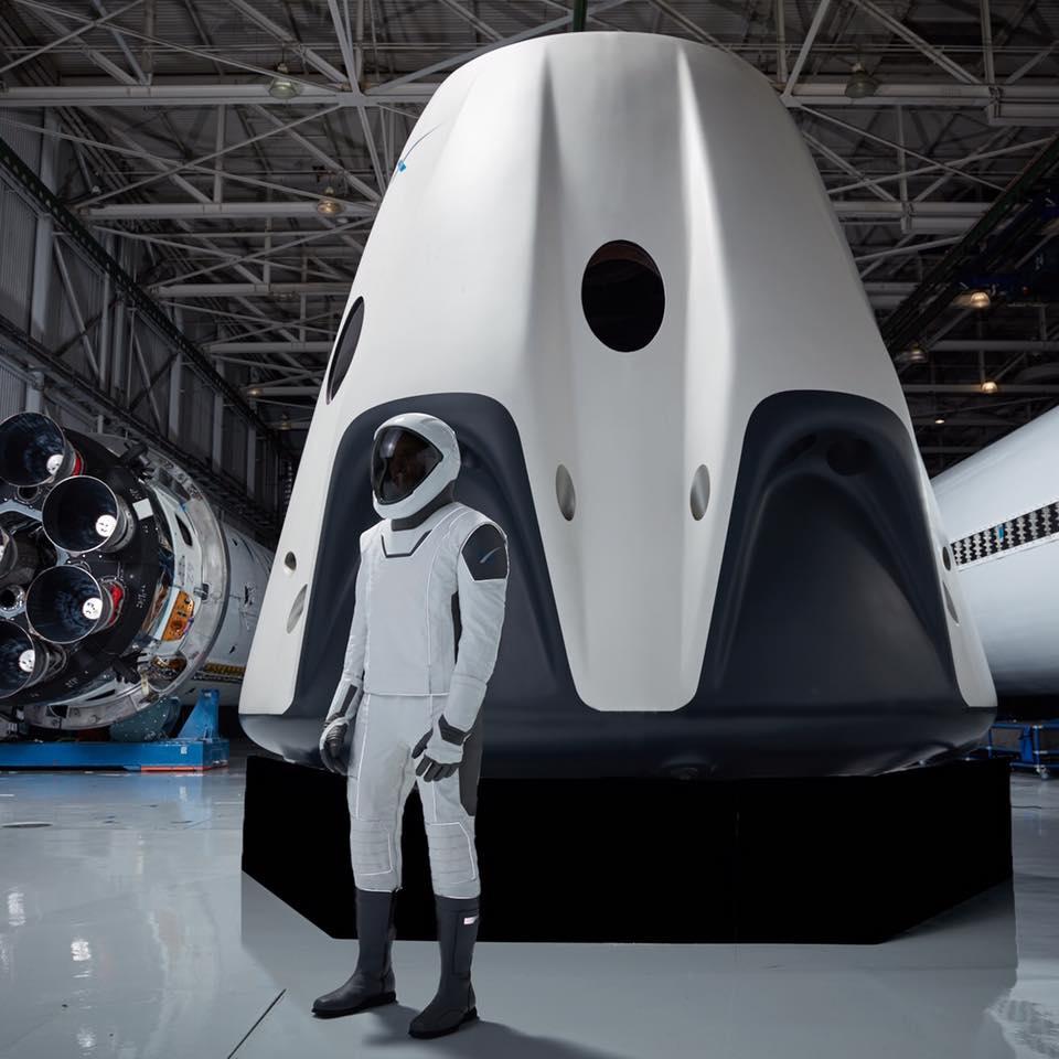 Skafander kosmiczny zaproponowany przez SpaceX, w tle Dragon Crew, czyli załogowa wersja statku.