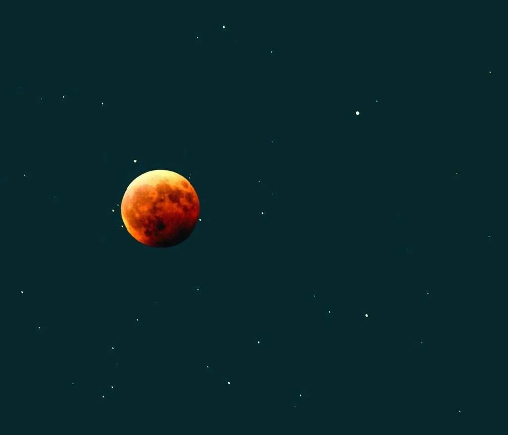 Zaćmiony Księżyc na tle Bliźniąt