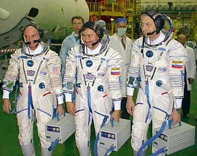 Kosmonauci i turysta przymierzają sprzęt