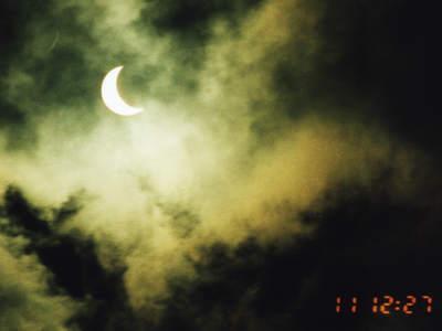 Zaćmione Słońce widziane przezchmury
