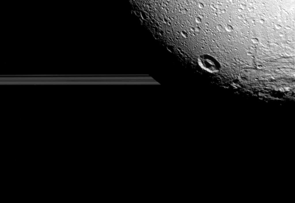 Dione na tle pierścieni Saturna